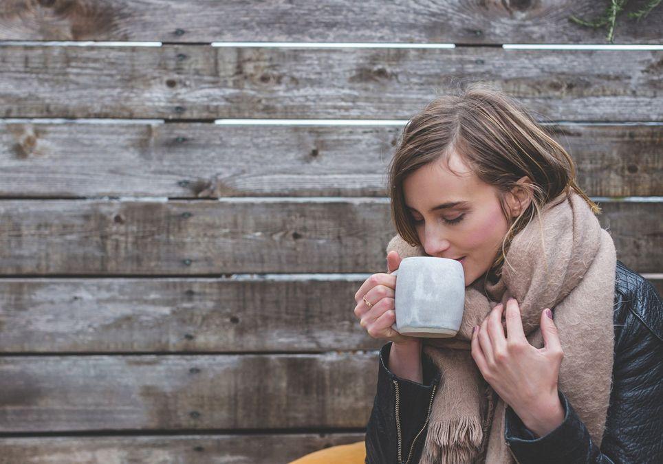 Mujer que pasa frío y se toma un café
