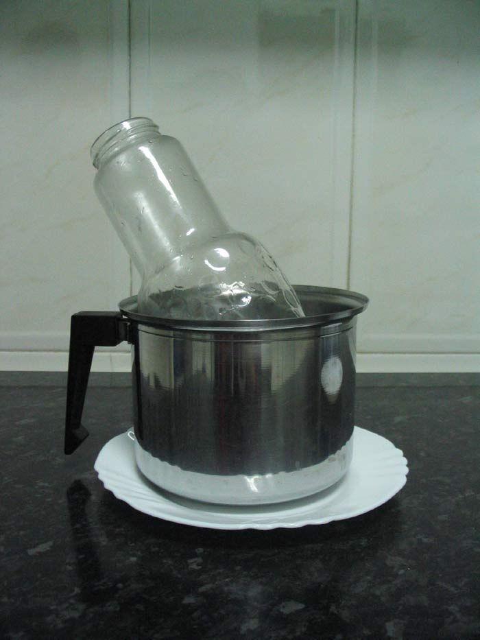 Botella o recipiente base de cristal transparente y recipiente-1, en este caso de metal con agua caliente en su interior.