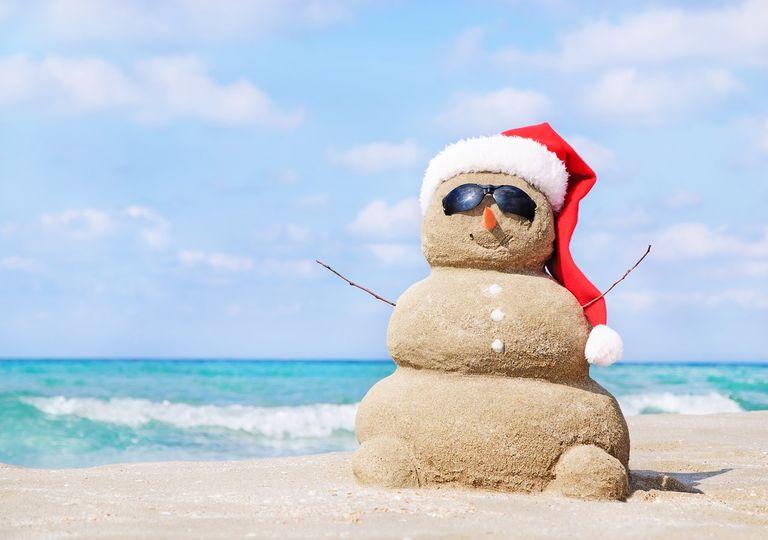 Muñeco de arena en la playa vestido con gorro de viejo pascuero