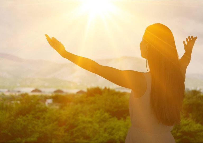 Mulher abraça pôr do Sol bem vindo calor