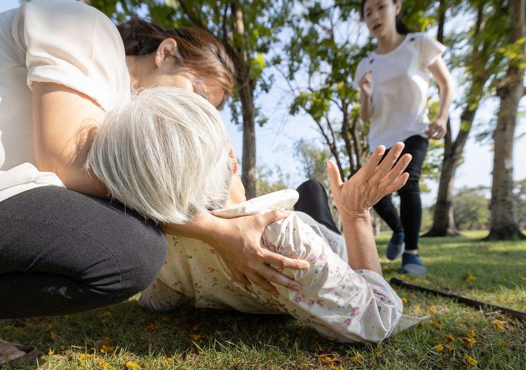 Adulto mayor caído en el suelo; personas la ayudan
