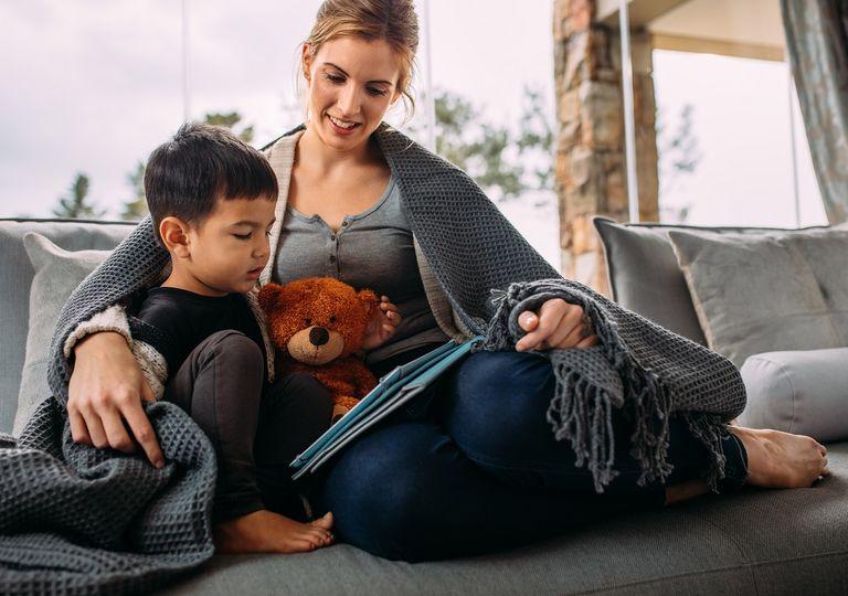 Madre e hijo sentados bajo una manta leyendo