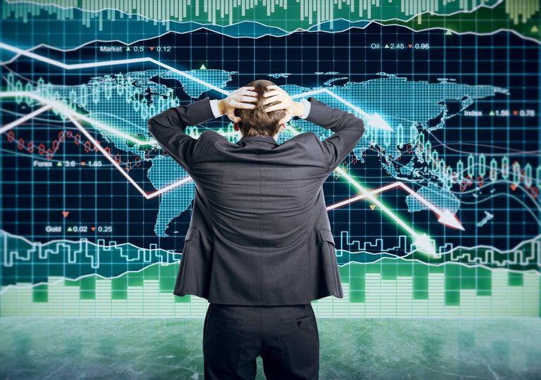 Homem de costas a observar gráfico mundial de ações.