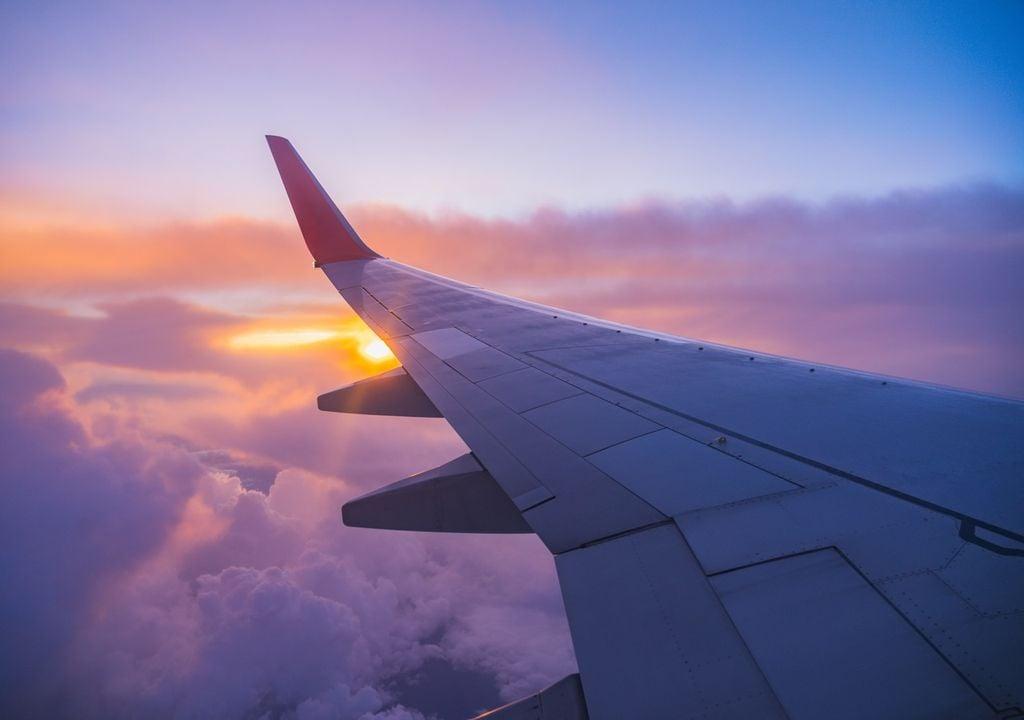 Vista de una ala de avión que vuela sobre las nubes con el Sol en el horizonte