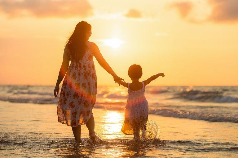 Madre e hija paseando por la playa durante el atardecer