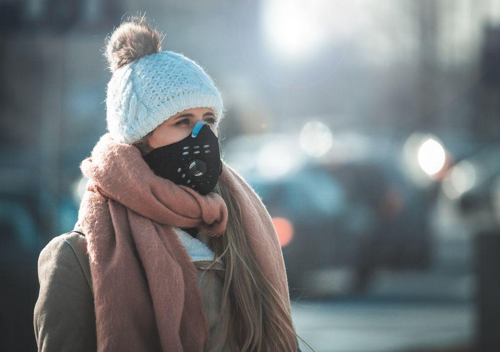 Mujer usando mascarilla en invierno