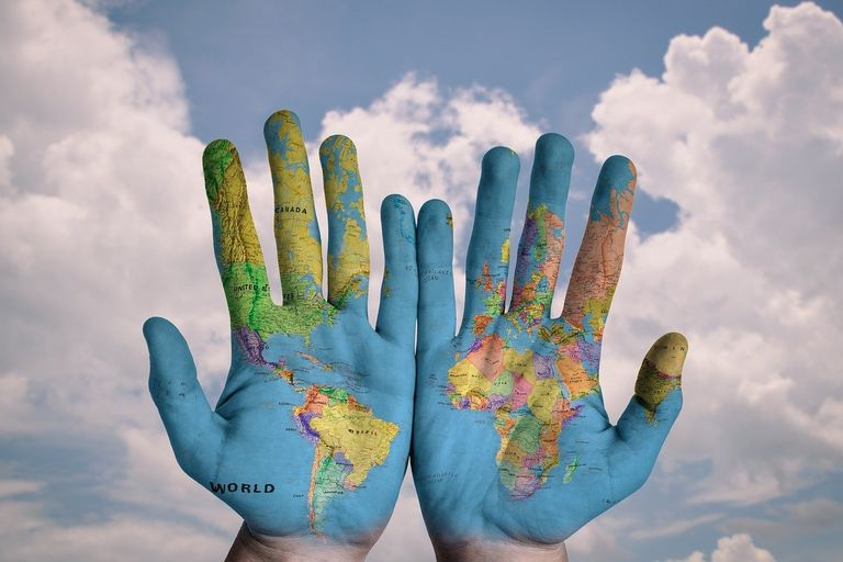Mapa mundi pintado sobre manos abiertas y cielo de fondo