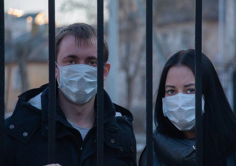 Dos personas con máscaras detrás de una reja