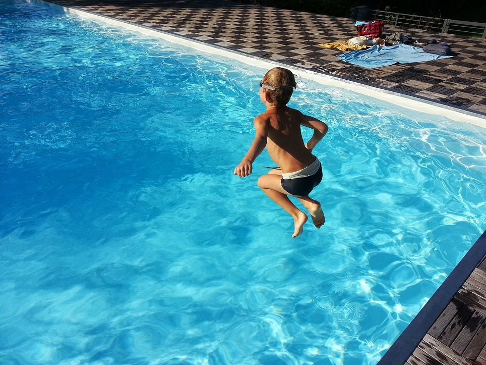 Niño saltando en la piscina