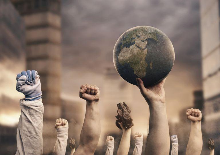 manos en alto afirmando el mundo en un ambiente contaminado