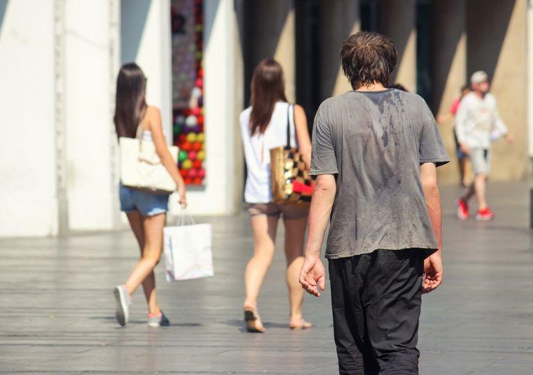 Hombre con calor caminando por el centro de la ciudad