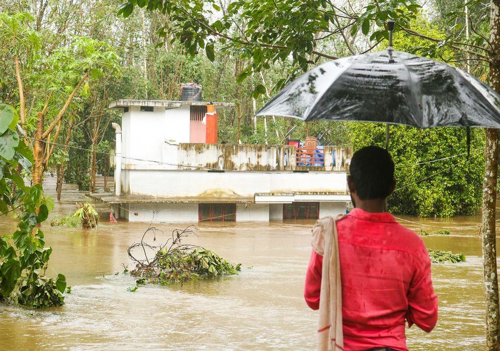 Persona con paraguas contemplando su casa inundada