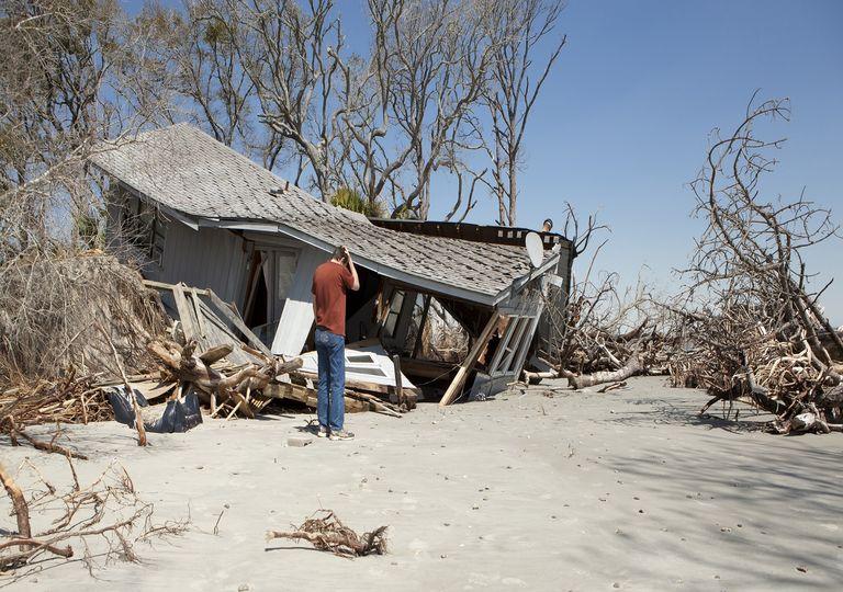 Persona mirando su casa después del paso de un huracán