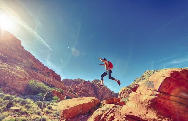 Joven saltando entre las rocas en un día soleado