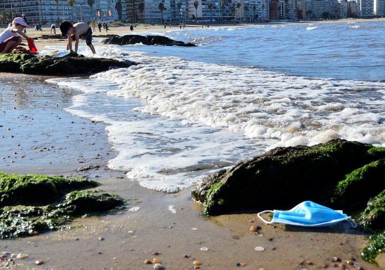 Mascarilla descartada en la playa; niños jugando