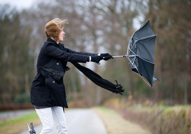 Mujer con paraguas volteado y fuerte viento