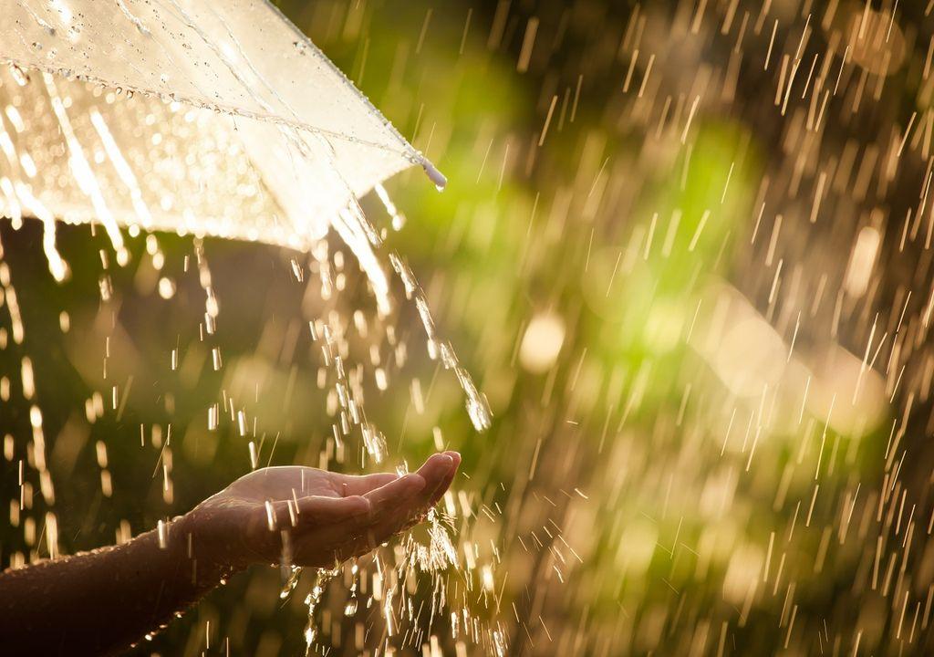 Mano femenina recibiendo gotas de agua; paraguas transparente bajo la lluvia