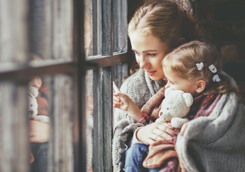 Madre e hija mirando hacia afuera por una ventana