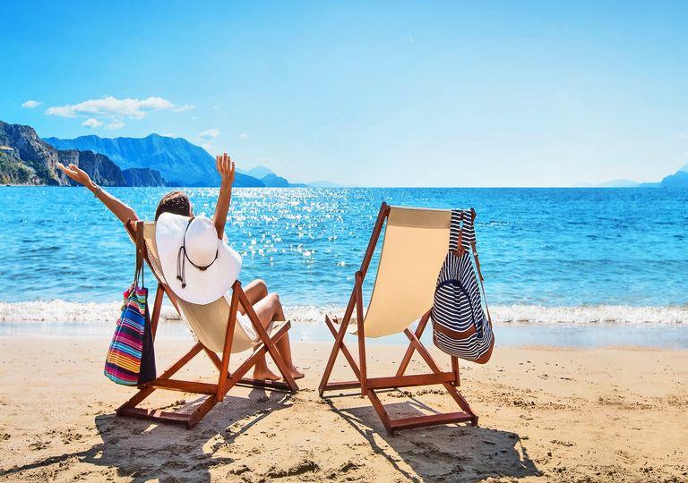 Mujer frente a la playa día soleado