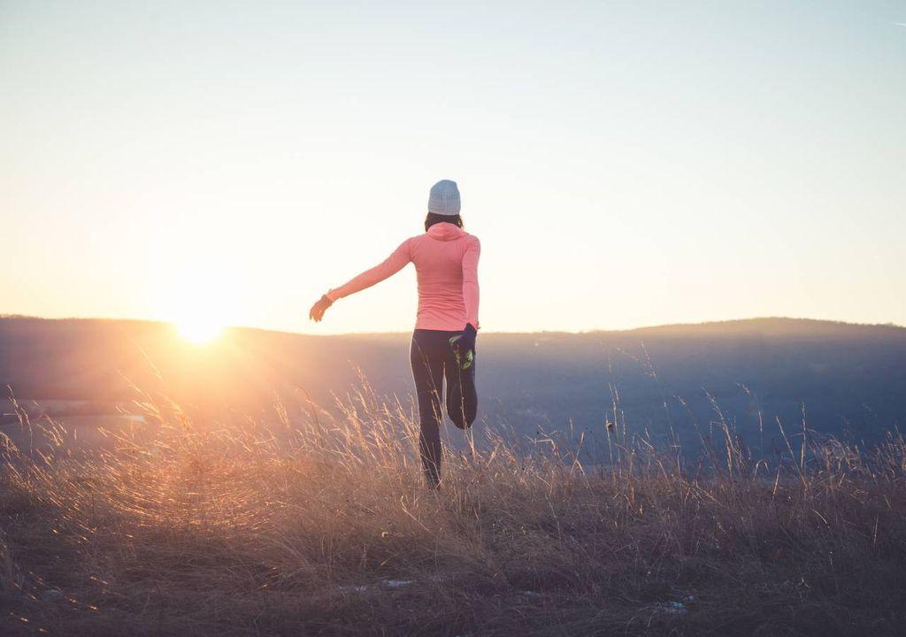 Mulher a exercitar-se com pôr do sol