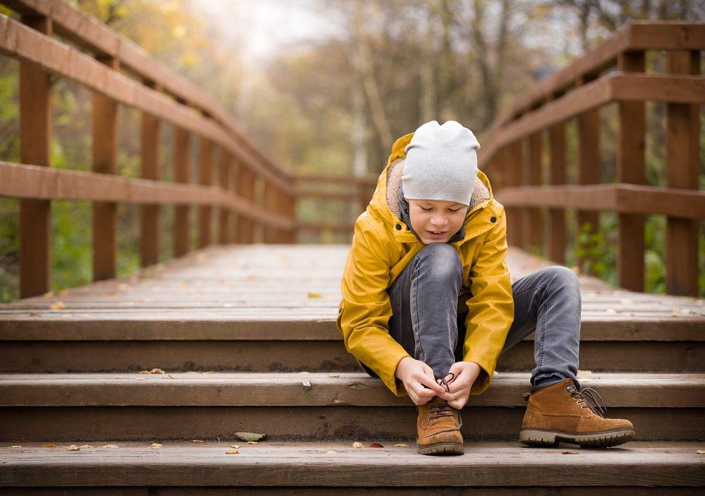 Niño sentado abrochándose el zapato en día frío