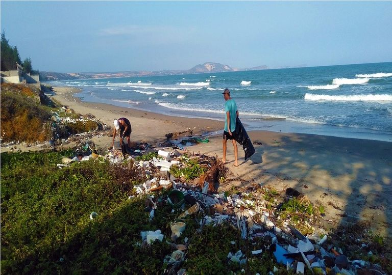 Personas recogiendo basura plástica en una playa