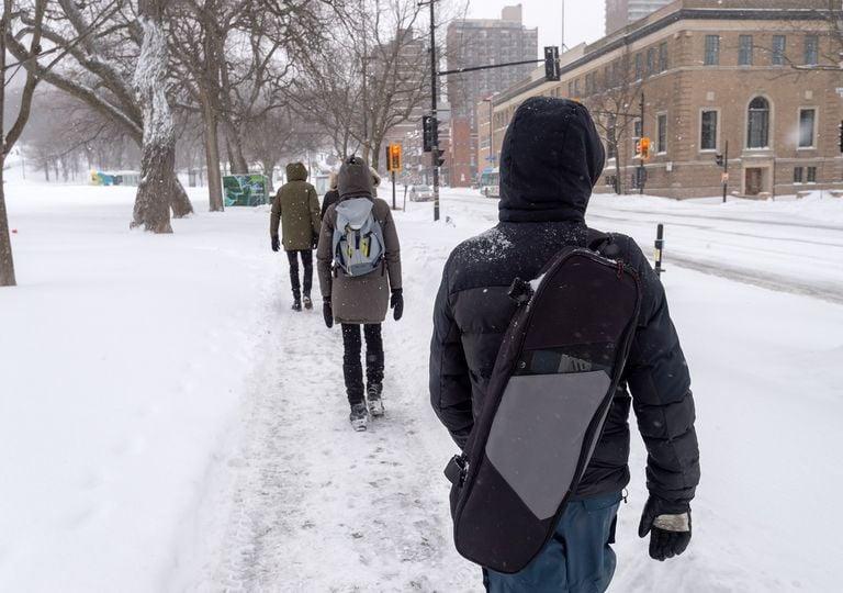Personas caminando en la nieve de la ciudad