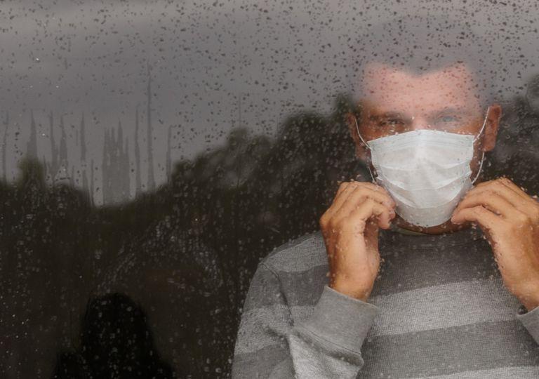 Persona con mascarilla mirando por la ventana
