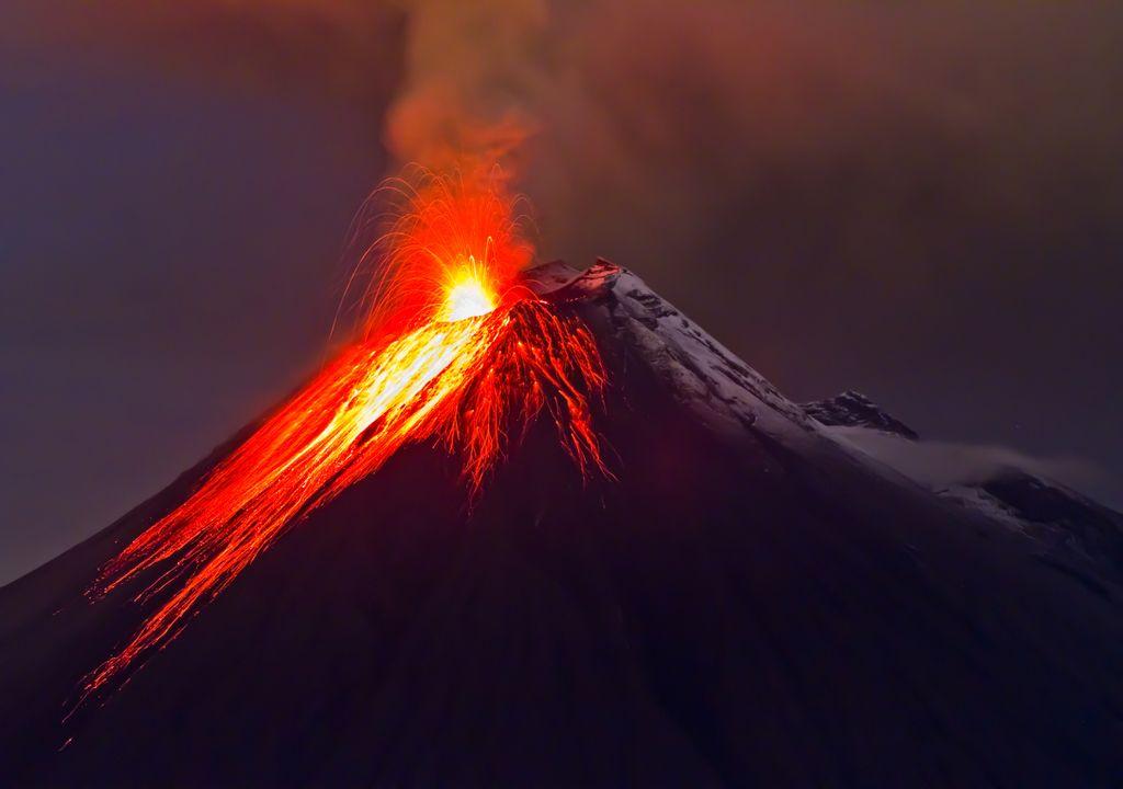 Volcan en éruption, avec des coulées de lave coulant sur la pente.