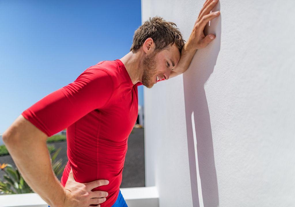Atleta contra la pared y calor sofocante
