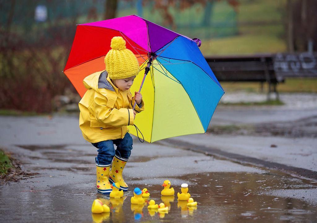 Niña con paraguas jugando sobre un charco de agua