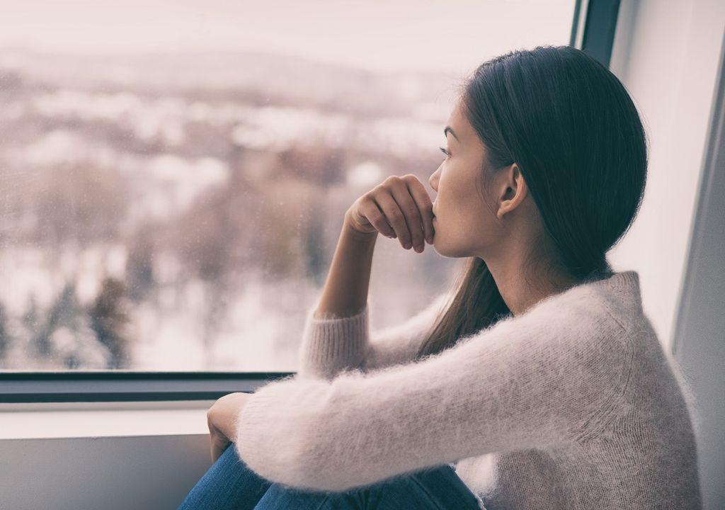 Mujer mirando preocupada el paisaje a través de la ventana