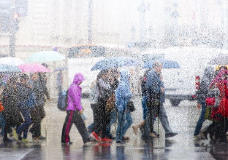 Personas cruzando la calle en día de lluvia
