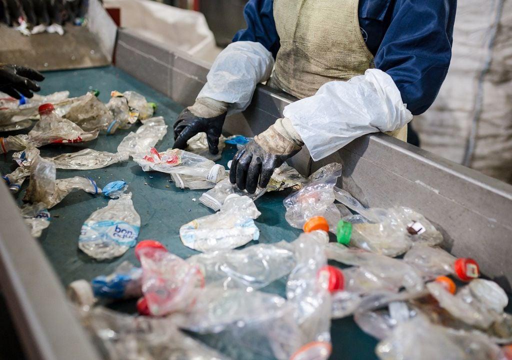Persona separando botellas plásticas; Planta de reciclado