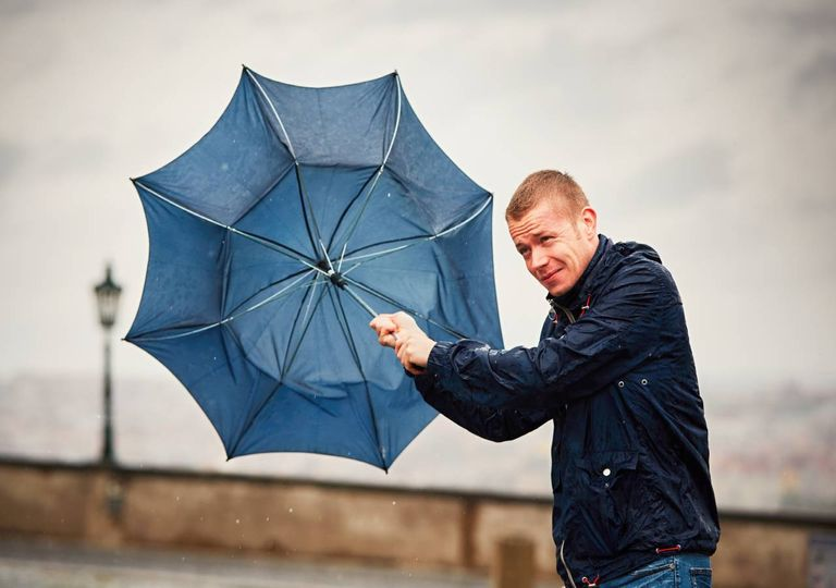 Homem a tentar segurar o guarda-chuva