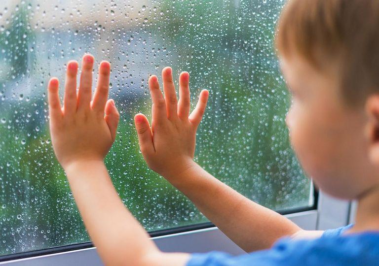 Niño con manos en la ventana, mirando la lluvia afuera