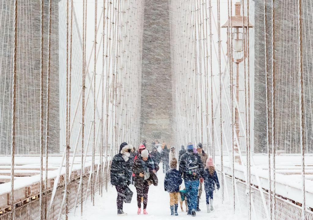 People walking across Brooklyn Bridge in a blizzard © Rudolf Sulgan