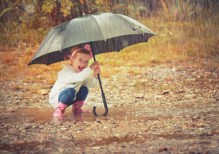 Stepping in puddle with umbrella during rainfall.