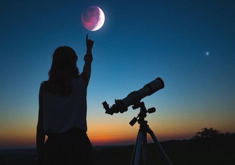 Rapariga com telescópio e eclipse lunar