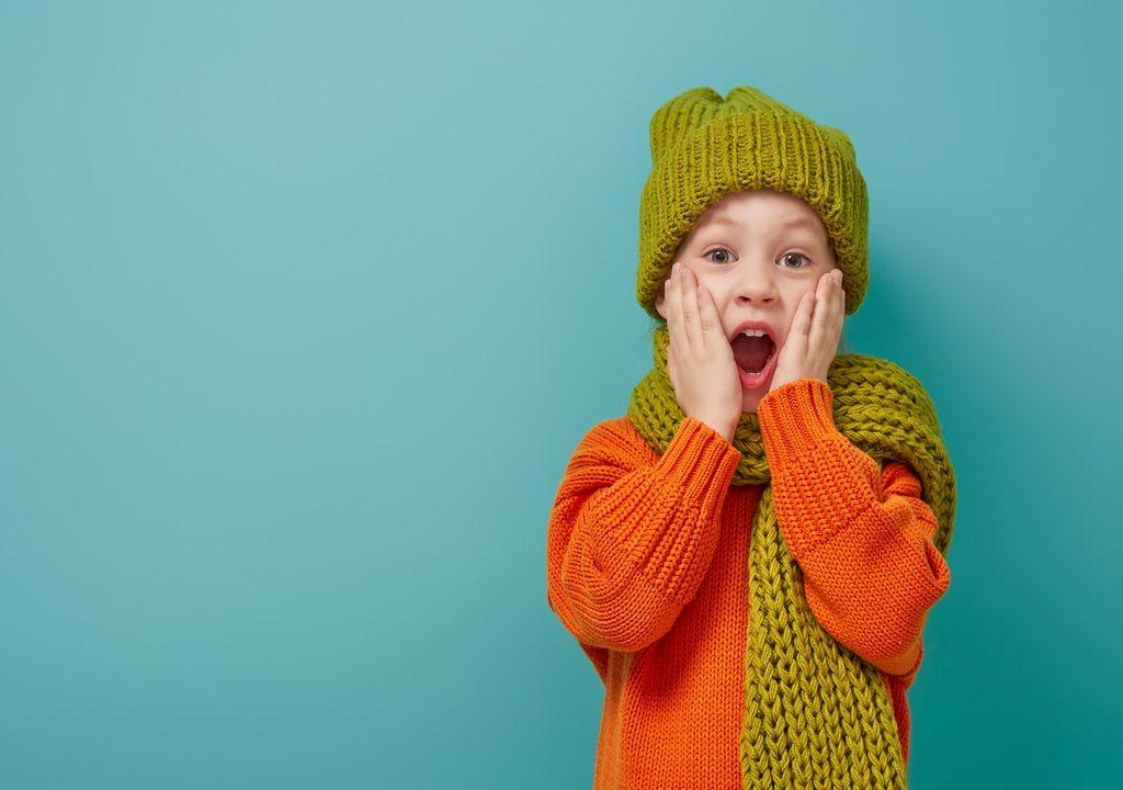 Niño sorprendido vestido con gorro y bufanda