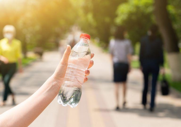 Persona afirmando una botella de agua en sus manos; Días de calor en las ciudades