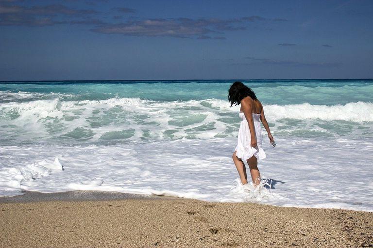 mujer vestida de blanco con los pies en el mar