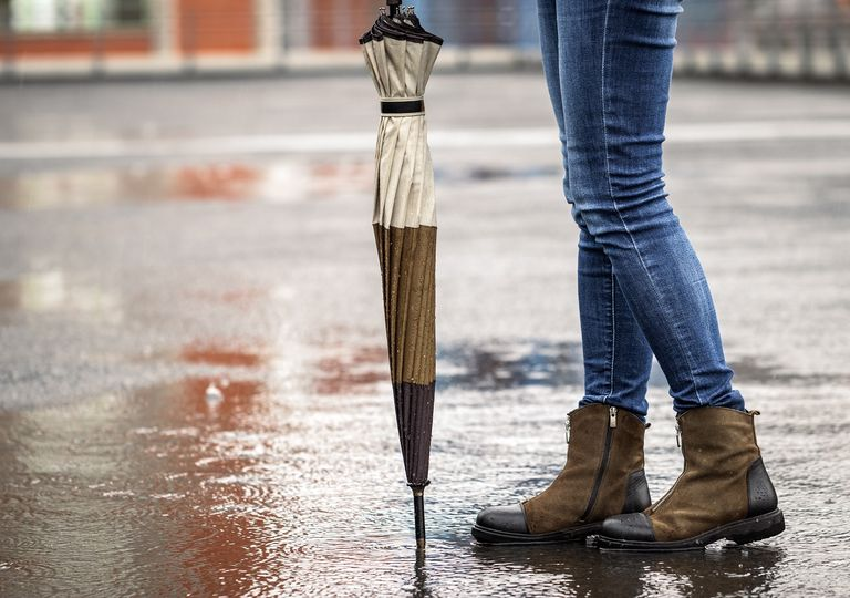 mujer en pie bajo la lluvia