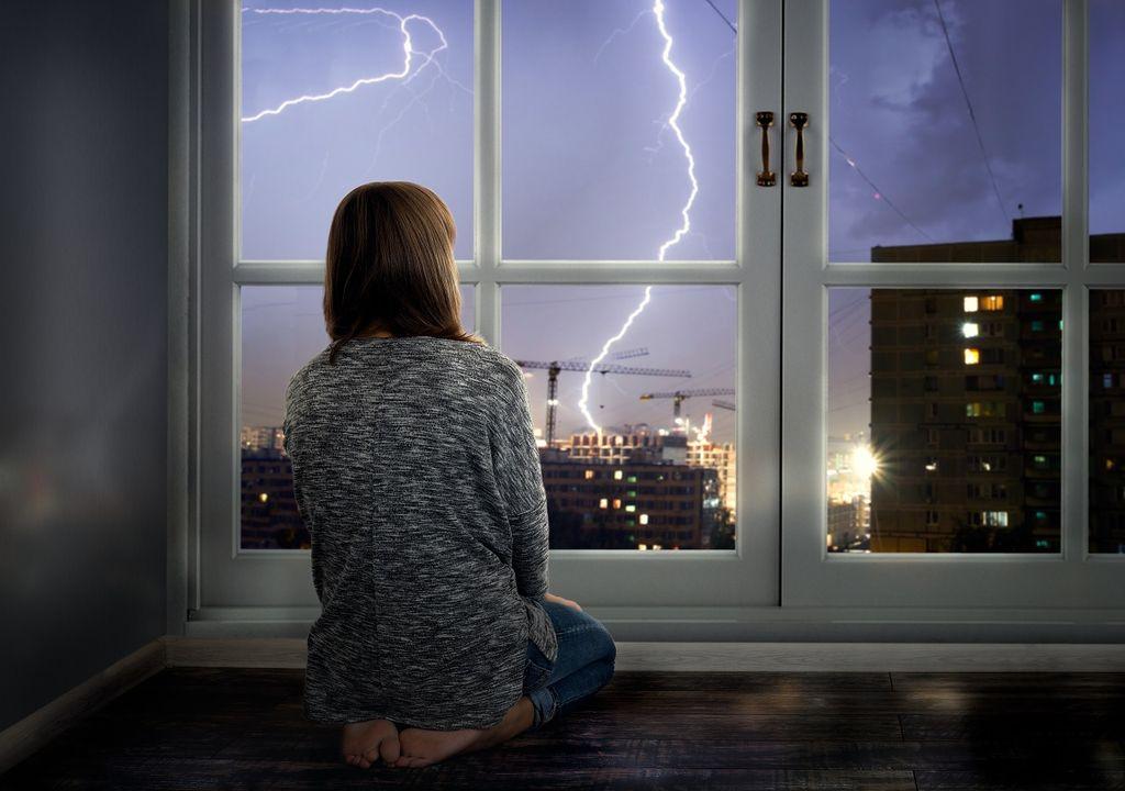 Mujer mirando un rayo por la ventana