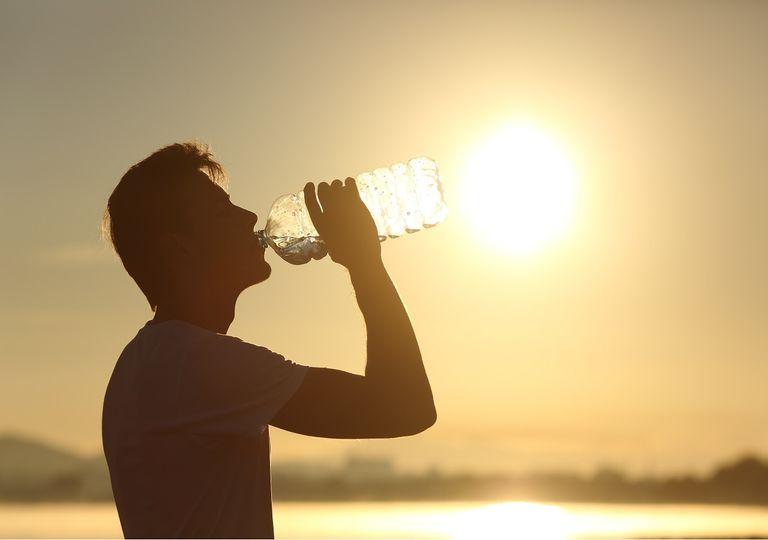 Hombre bebiendo agua con el sol de fondo