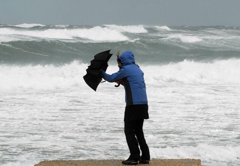 mujer con sombrilla en el viento