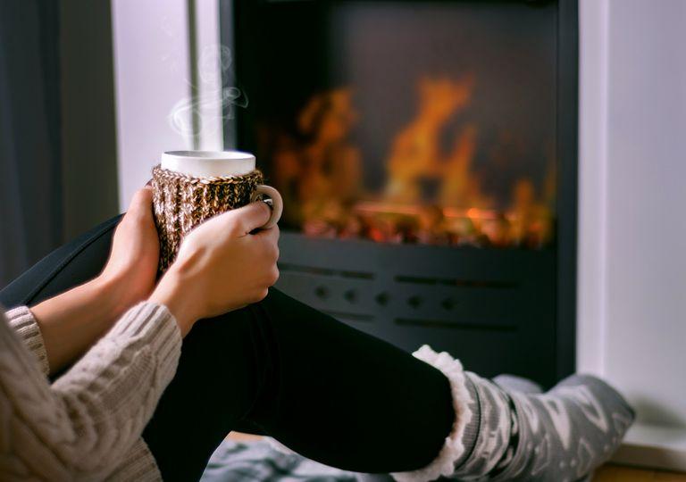 Mujer sentada frente al fuego con una taza en sus manos