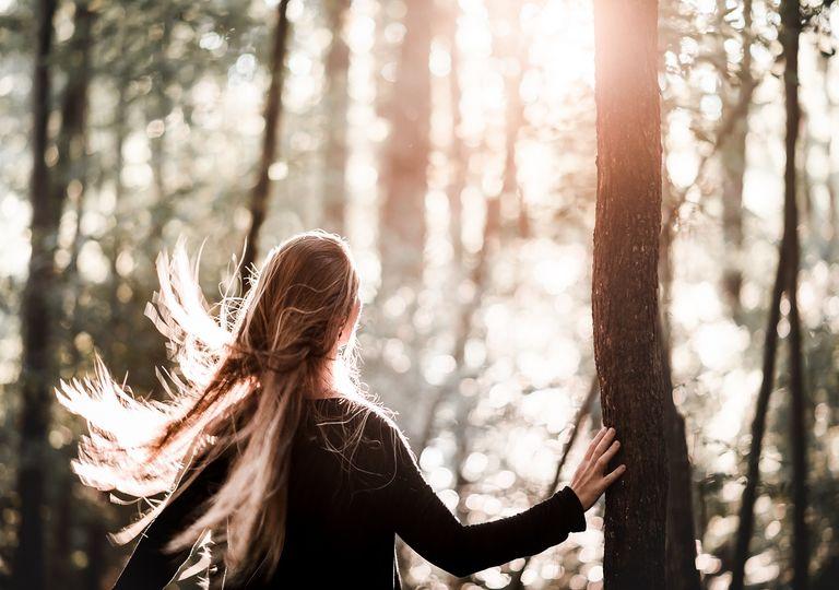 Mujer en un bosque contemplando el atardecer