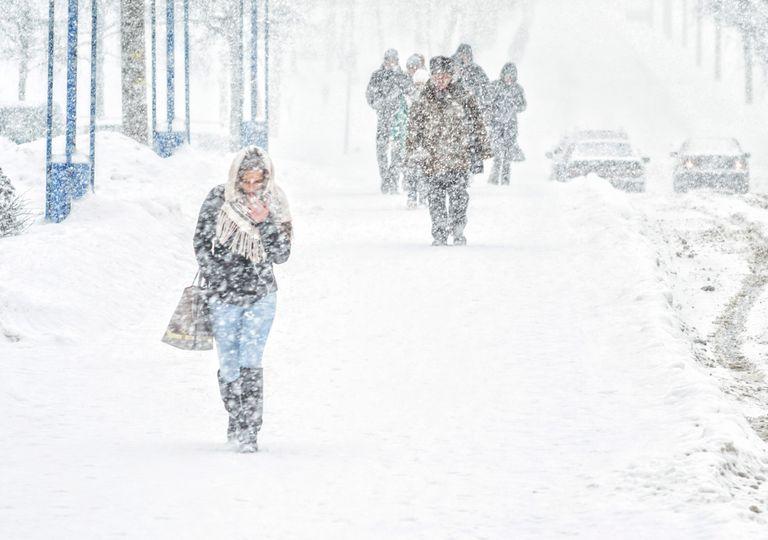Nevando y gente andando por la calle