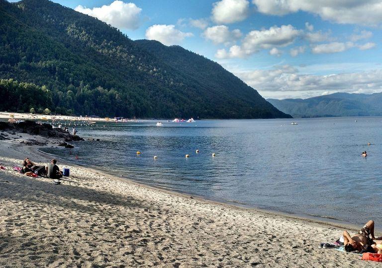 Personas descansando y bañándose en el Lago Caburgua